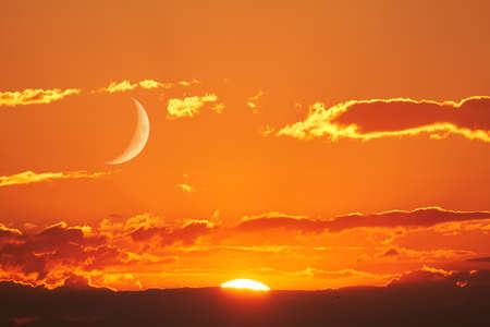 red and gold: The sun and the moon can be seen in the sky Simultaneously. Stock Photo