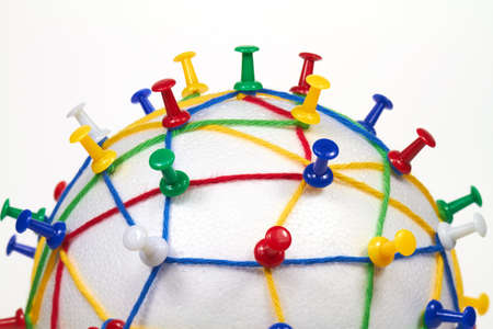 pin board: Colorful wool threads on a globe form a network between pins.