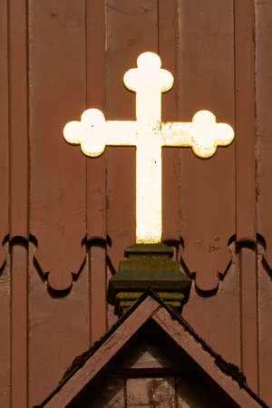 gold cross: Above the main entrance of a church is a shining gold cross.