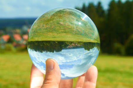 A hand holding a crystal ball in the sunlight.