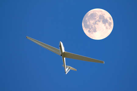 drive through: A sailplane in front of a blue sky glides through the air without its own motor drive. Stock Photo