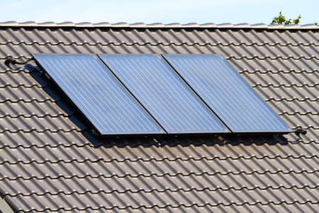 A solar collector on a roof creates warm water for solar heating. Stock fotó