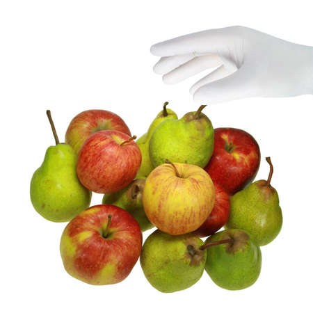 A hand in a white glove grabs a fruit. Stock Photo