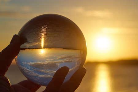 太陽が沈むドイツの川と照らされて水晶玉。 写真素材