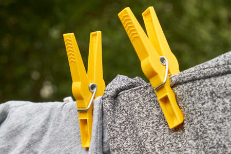 Garments hang dry on a clothesline and are held in place by clothespins.
