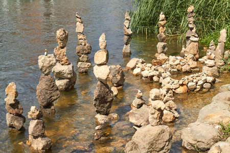 On a river bank stones have been stacked to towers.