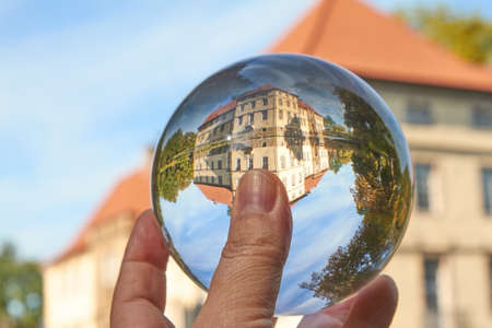 Well maintained medieval moated castle viewed through a glass ball.