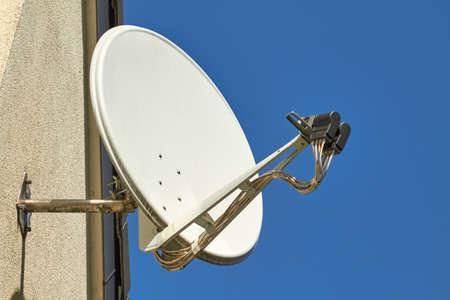 Eine Satellitenschüssel an einer Hauswand. Standard-Bild