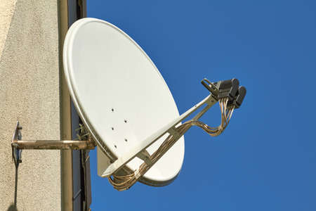 Una antena parabólica en la pared de una casa. Foto de archivo