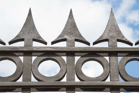 Black tips of a massive iron fence. Standard-Bild - 130813497