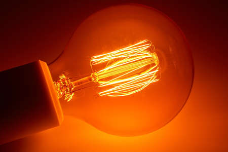 Old electric light bulb with orange luminous glow spiral.
