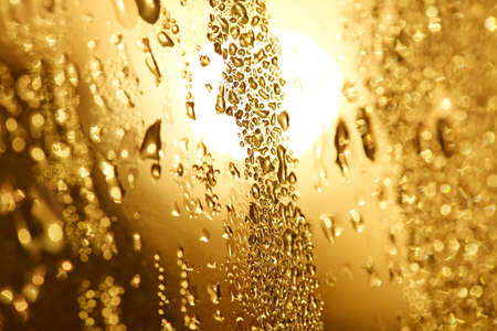 Small dewdrops on a glass pane in the sun.
