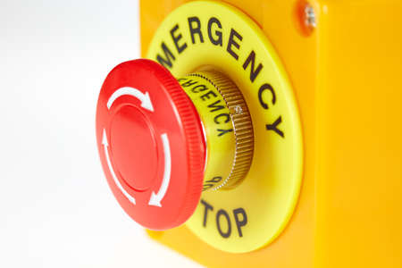 Red button in a yellow case with the label EMERGENCY STOP. Foto de archivo