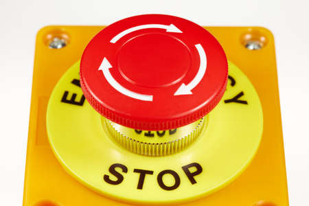 Red button in a yellow case with the label EMERGENCY STOP.
