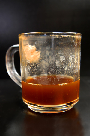 Dirty glass filled with coffee on a dark background