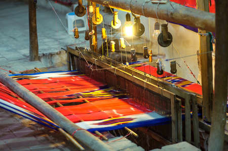 handloom: The weaving loom, is weaved a bright, red Persian carpet Stock Photo