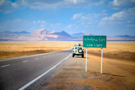 Road signs in Iran, are written on Farsi, around stony brightly orange desert, mountains and the blue sky are expensive, the car costs at the road
