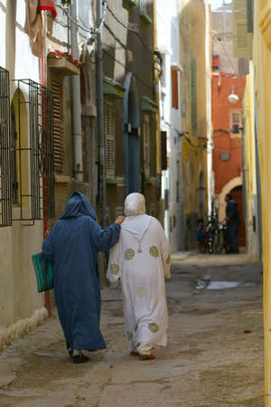 hassock: two persons in national clothes, go down the street the old city to Morokko Stock Photo