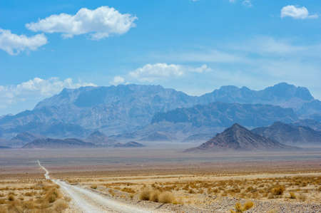 road through the stony desert going to a distance, on the horizon majestic ridges tower Stock Photo