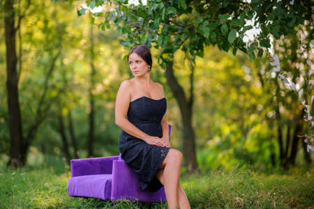beautiful girl sits on a lilac chair in the wood at sunset