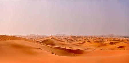 the orange dunes of the Sahara Desert leaving to the horizon. The dawn beginning over the desert Stock Photo