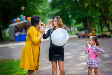 the girl with mother and the grandmother walks on the park, play and eat cotton candy
