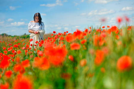 the beautiful girl with thoughtful a look walks in the poppy field