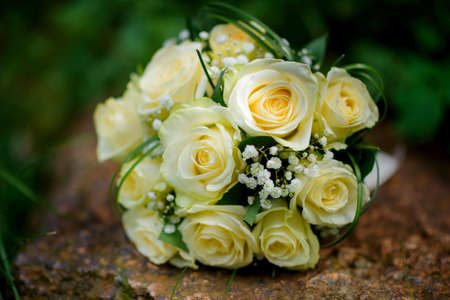 religious clothing: bouquet from gentle roses lying on the earth against the background of greens Stock Photo