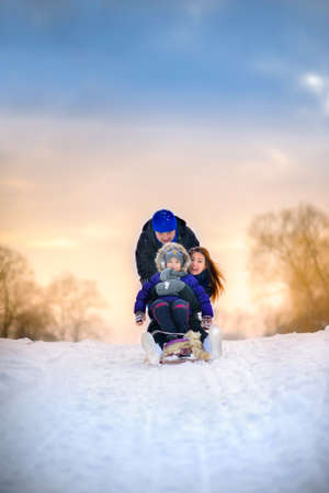 happy family rides the sledge in the winter wood, cheerful winter entertainments, everything is covered with snow around Stock Photo