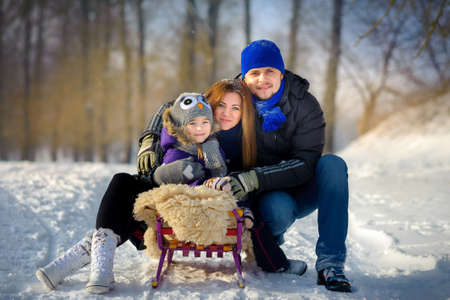 the happy close-knit family poses on the sledge in the winter wood Stock Photo