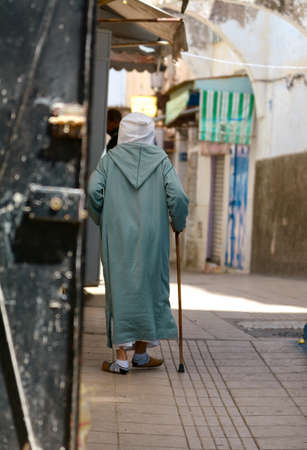 vestidos antiguos: elderly person in national clothes, goes down the street the old city to Morocco