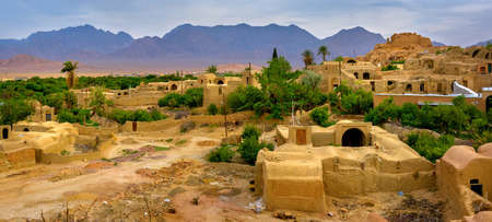 The village of clay houses in an oasis in the middle of the desert in Iran, on a background mountains tower Stock Photo