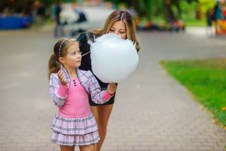 mother plays with the daughter in parky and eat cotton candy