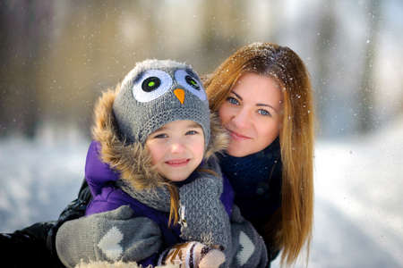 mother embraces the daughter and together smile for the camera, beautiful snow falls, a close-knit cheerful family, parents together with the daughter, on the eve of a holiday of Christmas Stock Photo