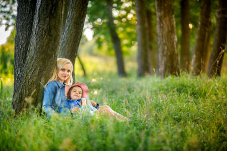 girl embrace mother outdoors, manifestation of tender feelings and care, smile each other, a close-knit family, the relations of children and parents Stock Photo