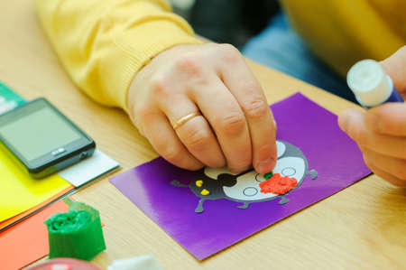 god's cow: teacher helps to make a hand-made article, at a fine arts lesson, a Gods cow on the lilac sheet of paper