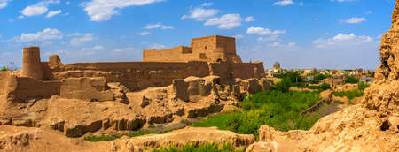 old clay fortress at hill top, over the city of Meybod in Iran, the fortress and the city from clay of orange color, on the sky float white clouds Editorial