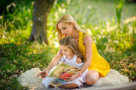 mother in a beautiful dress together with the daughter read the book sitting on a grass, a close-knit happy family, the relations of parents with children