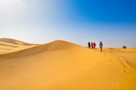 Sand dunes in the Sahara Desert, group of travelers goes on a dune crest, Merzouga, Morocco