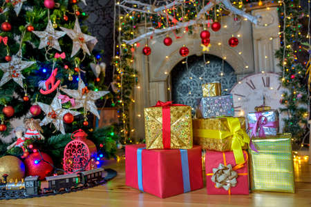 Christmas gifts lying under a fir-tree a set of multi-colored garlands and toys. Christmas mood