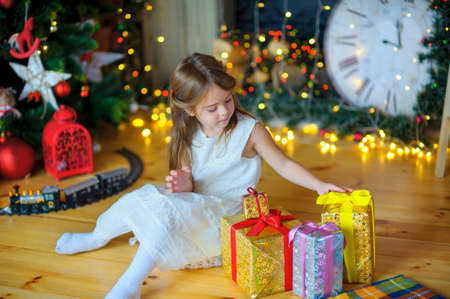 Christmas, expectation of a holiday, happy girl sits near a fir-tree, holds in hand Christmas gifts, a fir-tree with bright festive sparks on a background