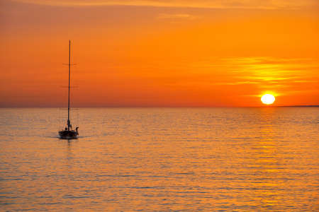 pacification: yacht comes back to the harbor at sunset, tranquility and a pacification