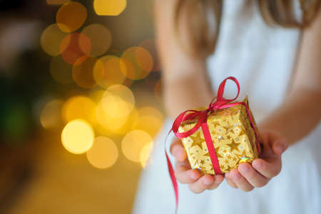 child gently holds in the hand a Christmas gift, the small gift box which is tied up by a red tape on a background a set of bright sparks, soft focus Stock Photo