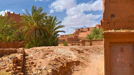 Moroccan village in the southern part of the country, clay walls of saturated orange color, in the foreground of a palm tree and a set of garbage, on the right on a wall prints of childrens hands