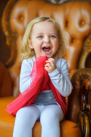 cheerfully: beautiful little girl, played and cheerfully laughs, joyful emotions