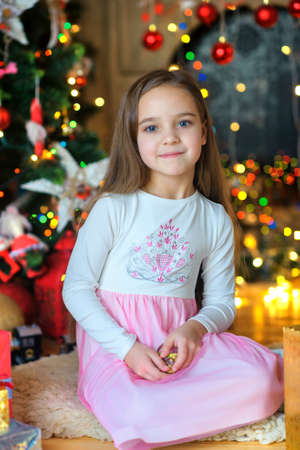 considers: happy little girl, sits on a floor near a festive fir-tree, chooses and considers gifts. Waiting for a holiday.