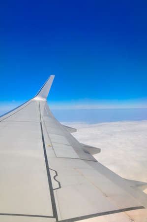 view from the plane on a wing and the earth covered with clouds