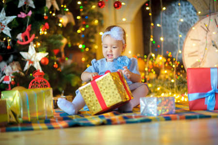considers: beautiful little girl, sits on a floor and considers Christmas gifts. Bright festive fires on a background. Waiting for a holiday. Stock Photo