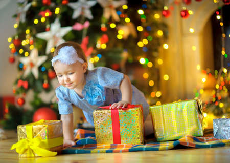 considers: beautiful little girl, creeps on a floor and considers Christmas gifts. Bright festive fires on a background. Waiting for a holiday.