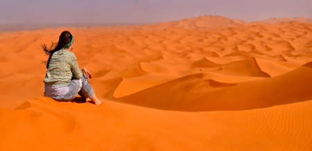 pacification: girl in a pacification sits on a sandy dune, looks at the desert avoiding to the horizon, dismissal vanity